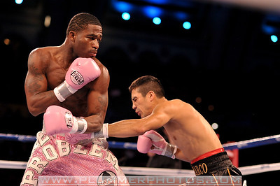 ANTONIO DEMARCO attempts to give ADRIEN BRONER (pink trunks) a shot to the body.