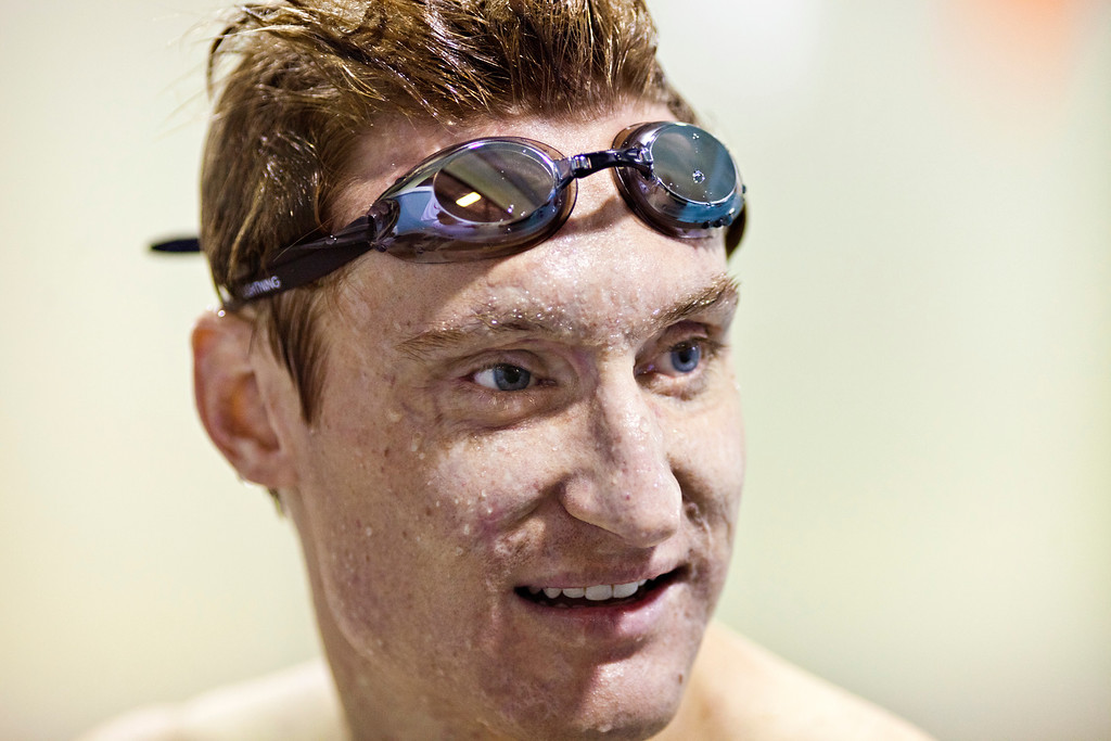 Paralympian Brad Snyder, who was blinded in an IED attack while serving in Afghanistan, pauses between laps to listen to instructions from Loyola University Maryland swim coach Brian Loeffler during a training session at the Meadowbrook Aquatic Center in Baltimore July 31.<br /> TOM McCARTHY JR. | CR STAFF