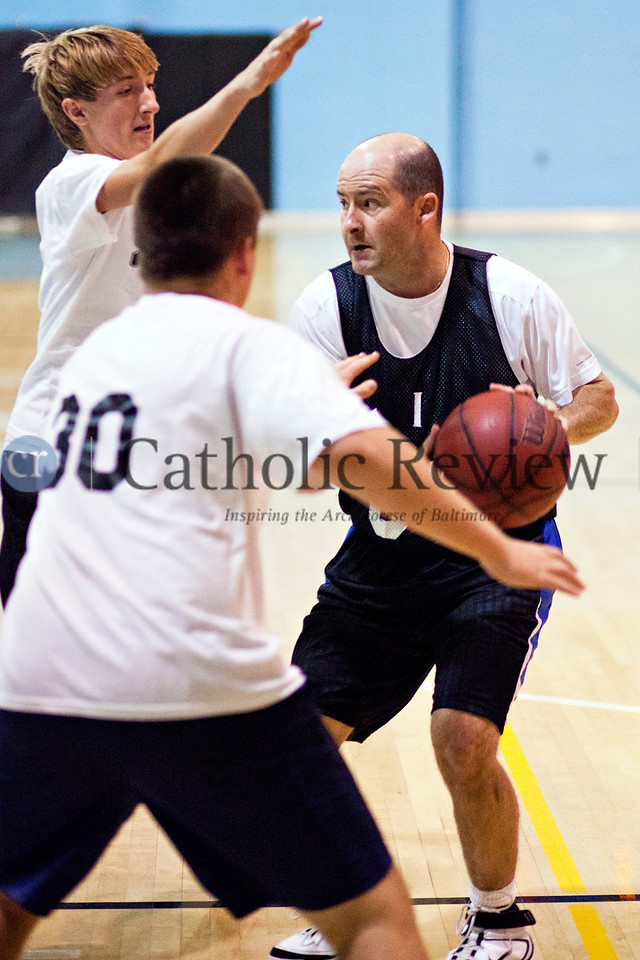 Father Jesse Bolger looks for a pass against heavey defense as priests and seminarians from around the Archdiocese of Baltimore take on parishioners in a hard-fought basketball game Sept 14.TOM McCARTHY JR. | CR STAFF