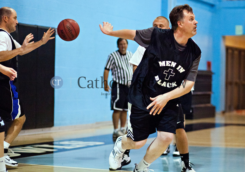 Father Brian Nolan makes a no-look pass to Father James Bolger as priests and seminarians from around the Archdiocese of Baltimore take on parishioners in a hard-fought basketball game Sept 14.TOM McCARTHY JR. | CR STAFF
