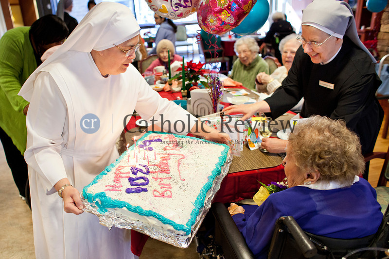 TOM McCARTHY JR. | CR STAFF<br /> Sister Lordes and Sister Lawrence Mary present a cake to Mary Rodenhi, a resident of St. Martin's Home for the Aged who celebrated her 102nd birthday Jan. 9.