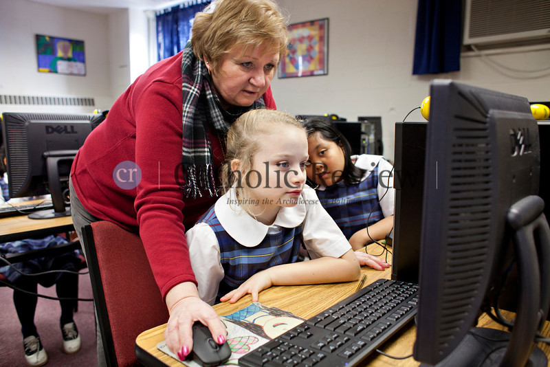 TOM McCARTHY JR. | CR STAFF<br /> St. Clement Mary Hofbauer School technology teacher Cathy Urban helps third-graders Allie Petryszak, 9, and Raisa Baccay, 8, use the Crusaders for Learning computer program to select a pen pal from a Catholic school in in a different part of the country Jan. 8.