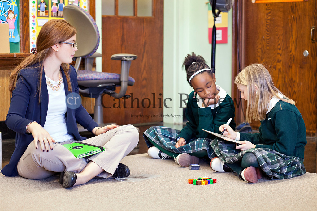 TOM McCARTHY JR. | CR STAFF<br /> Third grade teacher Kathleen Smith looks on as Kimoree Sanders and Maya Reynolds use counter blocks to do multiplication problems at St. Michael the Archangel School in Overlea Jan. 9.