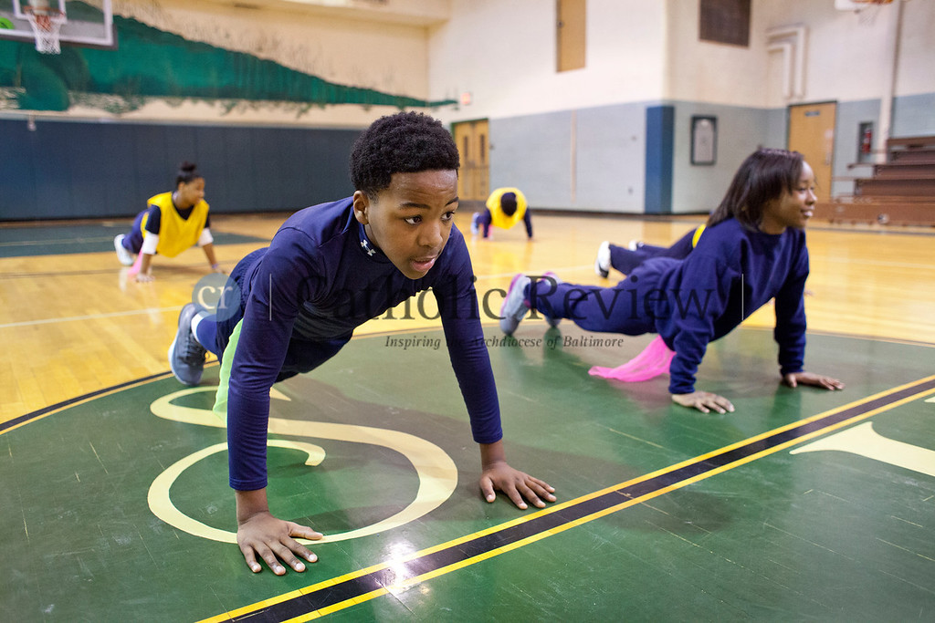 TOM McCARTHY JR. | CR STAFF<br /> Sixth-graders Desmond Cherry, 12, and Peyton Whitehead, 11, do push-ups during their physical education class at Holy Angels Elementary School Jan. 6.
