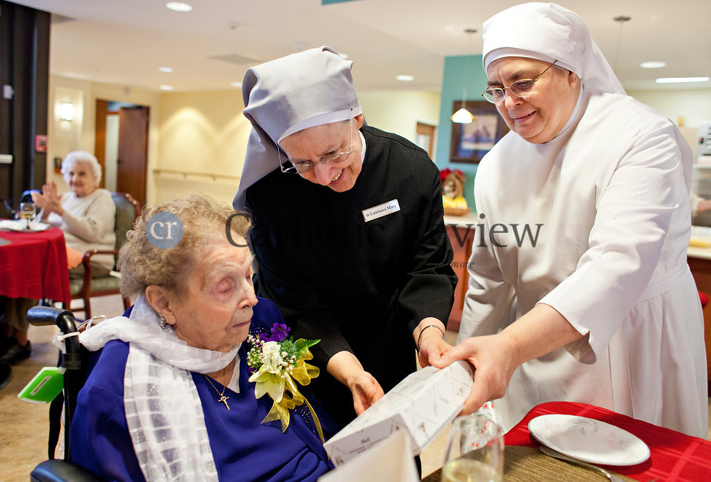 TOM McCARTHY JR. | CR STAFF<br /> Mary Rodenhi, a resident of St. Martin's Home for the Aged who celebrated her 102nd birthday Jan. 9, gets help from Sister Lawrence Mary and Sister Lordes unwrapping a gift of a box of chocolates.