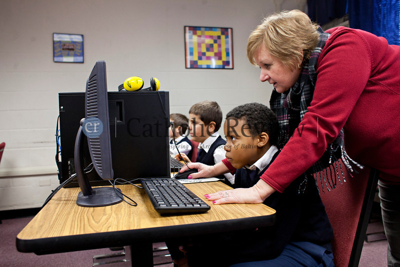 TOM McCARTHY JR. | CR STAFF<br /> St. Clement Mary Hofbauer School third-grader Ryan Johnson, 9, gets some assistance from technology teacher Cathy Urban as he uses the Crusaders for Learning computer program to select a pen pal from a Catholic school in Oklamhoma Jan. 8.