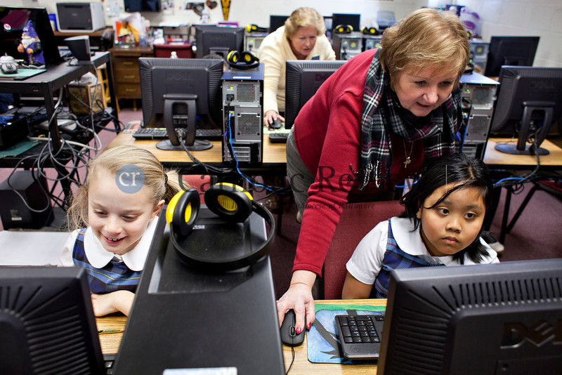 TOM McCARTHY JR. | CR STAFF<br /> Third-graders Allie Petryszak, 9, and Raisa Baccay, 8, get assistance from St. Clement Mary Hofbauer School technology teacher Cathy Urban using the Crusaders for Learning computer program to select a pen pal from a Catholic school in in a different part of the country Jan. 8.