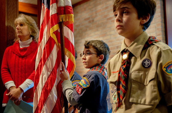 St. Louis School fifth-grader Andrew Fullone (left) holds the American flag as he and fourth-grader Michael Principe prepare to process into a Veteran's Day prayer service Nov. 8 at St. Louis Church in Pittsford, N.Y. (photo by Mike Crupi)