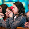 Meghan Bartholomay kneels in prayer at Brighton's St. Thomas More Church.