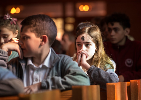 Tricia Toth kneels in prayer during the Liturgy of the Eucharist at Brighton's St. Thomas More Church.