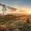 A German tourist takes in the views towards Stewart Island as the sun sets.