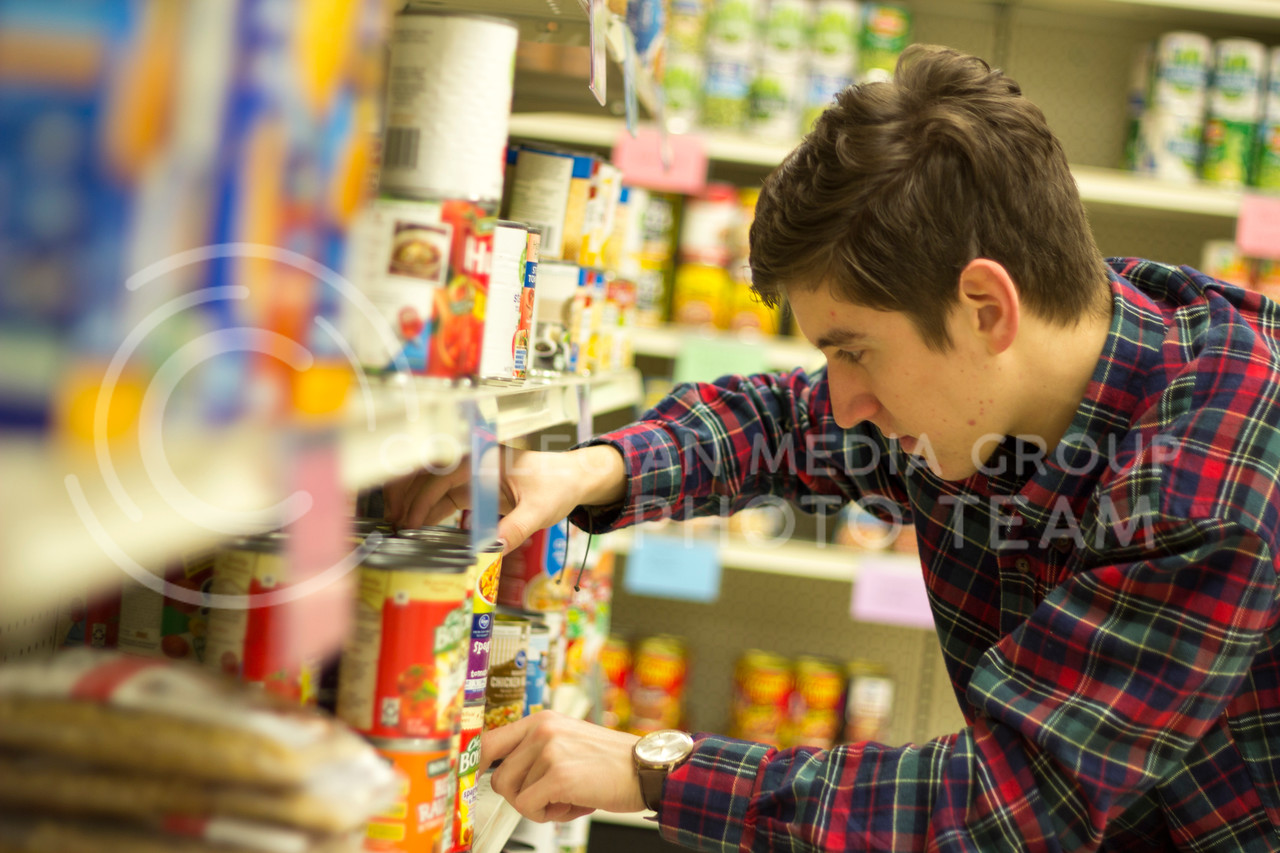 Jaden Castinado, Freshmen in Food Science and Industry Stocks and straightens shelves at Cats Cupboard in 009 Fairchild Hall. Jaden is one of the many volunteers that help to keep Cats Cupboard running. (Alex Shaw | Collegian Media Group)