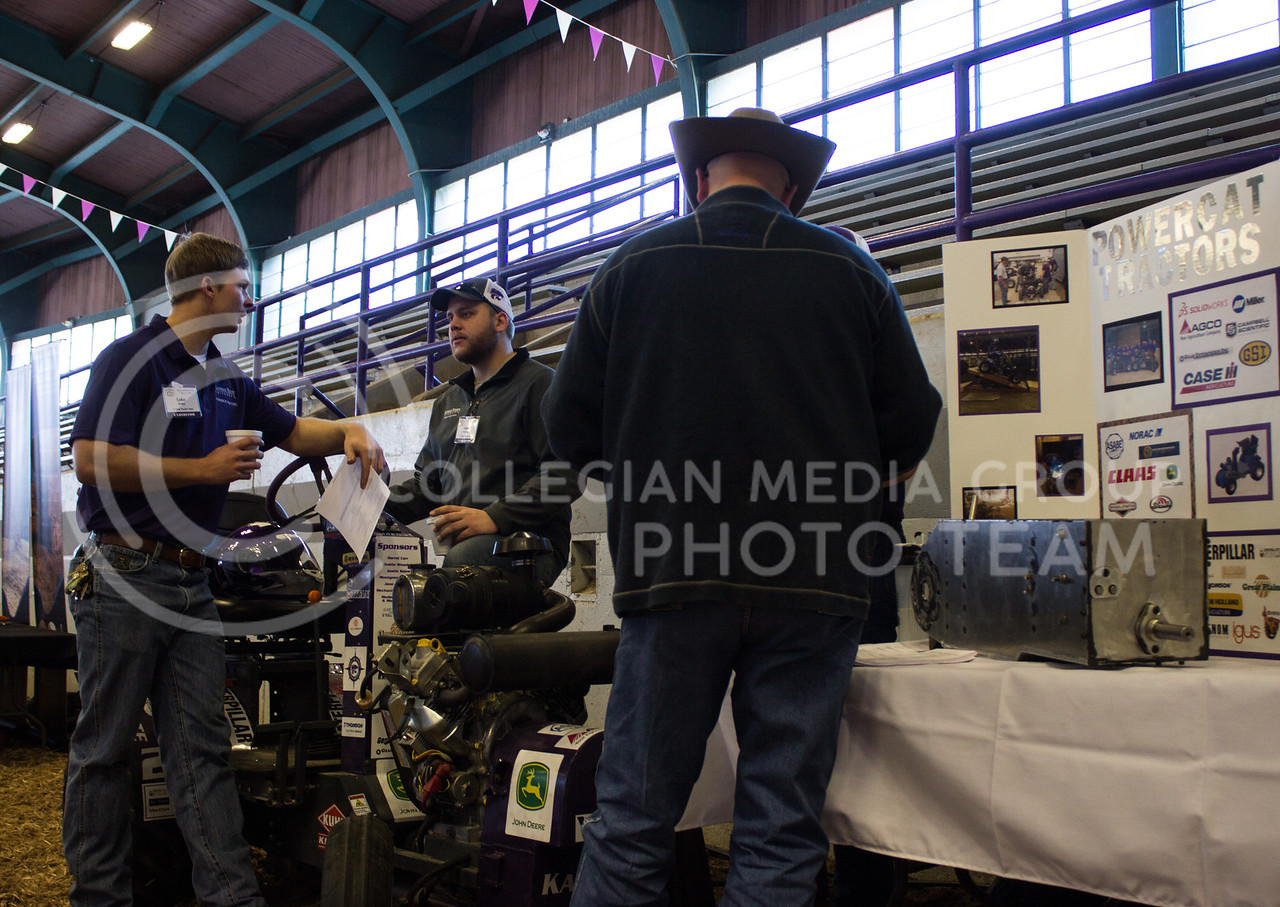 Luke Weller,  senior in biological systems engineering, and Gabe Bergmann, senior in agricultural technology management, stand by the 1/4th scale tractor they worked on in 2016. They were showing off the tractor in Weber Arena at Cattlemen's Day on March 3, 2017. (Regan Tokos | The Collegian)