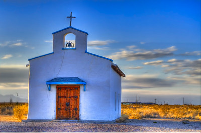 Little white desert church along side the road.