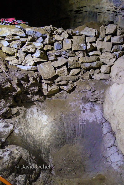 The lower pit to presumably capture drainage from the elevated pit delineated by the stone wall above it.