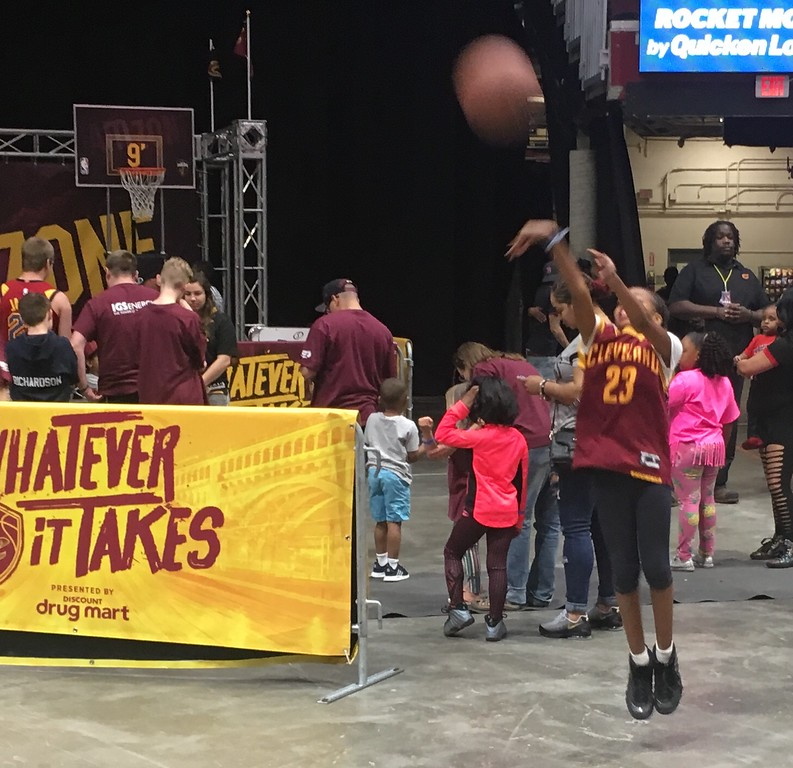 . Youtfhul shooter lets fly with a jumper at one of the baskets set up on the perimeter of the Cavs Watch Party at The Q. David S. Glasier - The News-Herald
