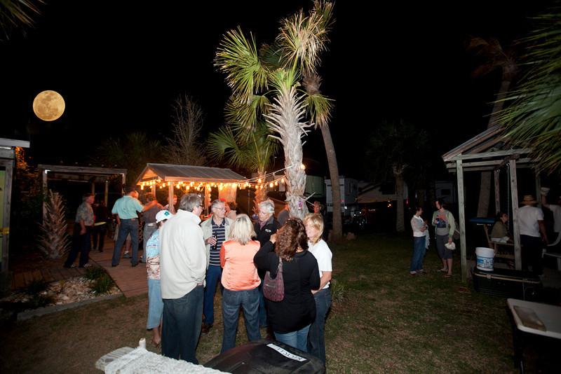 Large group enjoying the rising of the full moon outside the Hideaway Tiki Bar, Cedar Key Florida