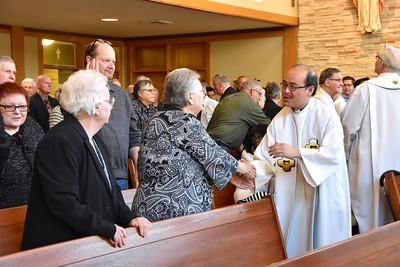 Fr. Quang shares the Sign of Peace with Fr. Bill's sisters
