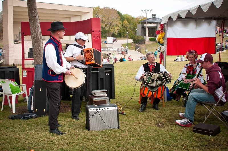 Musicians playing Polish music in front of the Polish Genealogical Society of Texas booth.