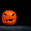 Creepy jack-o-lantern against a severe black background.