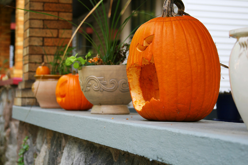 Classic front porch decorated with pots of flowers and, yes, creepy pumpkins!