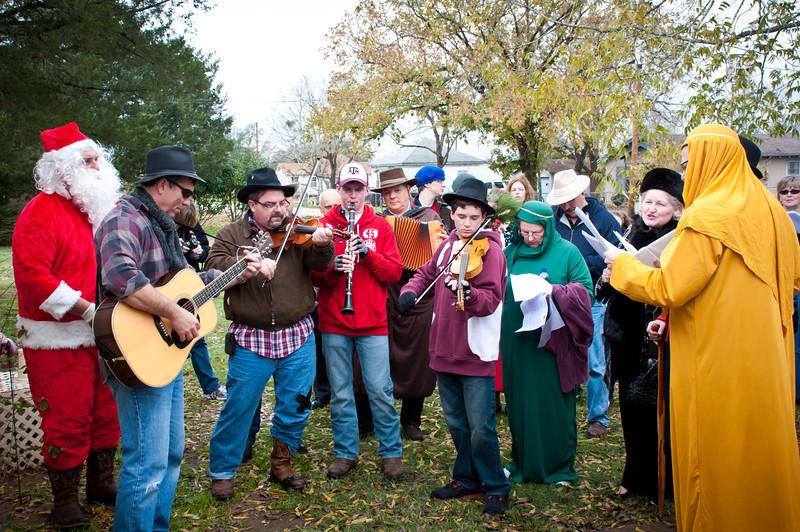 Musicians and carolers singing koledy.