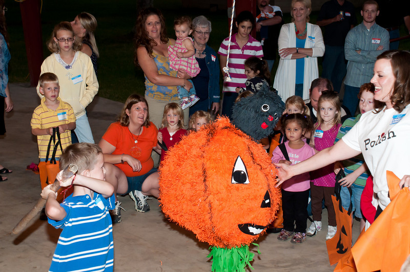 Children having fun hitting the big orange pinata.