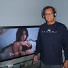 Spry Dennis with Bose headphones (birthday gift) in front of his big screen TV with Victoria's Secret model
