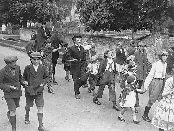 "<font size=3><u> - Carnival Parade - </u></font> (BS0264)  Brook street - carnival parade.1932?   John Lane, father of David Lane in clown's outfit leading the horse. Joan Walters wearing flying helmet and Jack Witney wearing raincoat and cap. Natalie Dancer writes ""Jack Witney became a member of my family. Taken in by my Great Grand-Parents Richard and Silvia Dancer."""