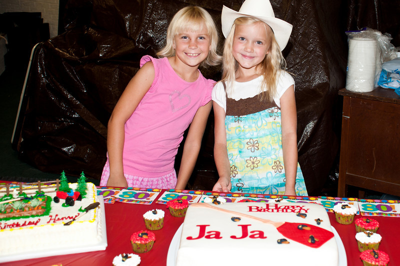 Two young ladies keeping an eye on the birthday cakes
