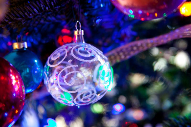 Transparent Christmas bulb on a blue-lit tree.