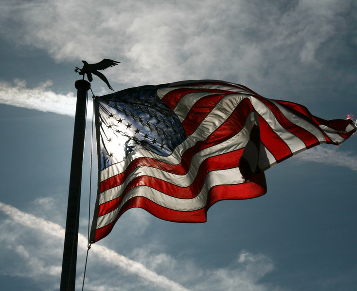 Old glory. The US flag waving against the sun in a brilliant blue sky.