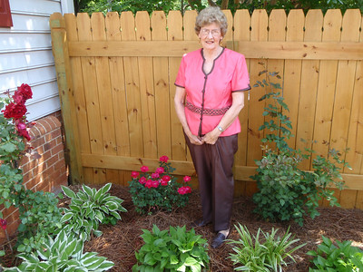 Mom in her patio garden with the new fence and Knock-Out rose bush provided by Lisa' (adopted daughter)