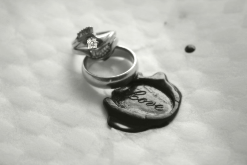 Soft focus on a stylish diamond engagement ring and wedding band set, LOVE wax seal as a backdrop.