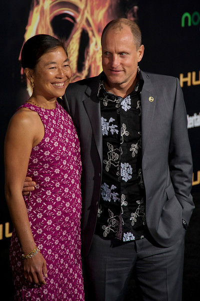 LOS ANGELES, CA - MARCH 12: Actor Woody Harrelson (R) and Laura Louie arrive at the premiere of Lionsgate's 'The Hunger Games' at Nokia Theatre L.A. Live on Monday, March 12, 2012 in Los Angeles, California. Photo taken by Tom Sorensen/Moovieboy Pictures.