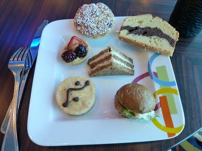 Afternoon tea: raisin scone, marble poundcake, berry tart, tuna sandwich, chicken sandwich, peanut butter cheesecake.