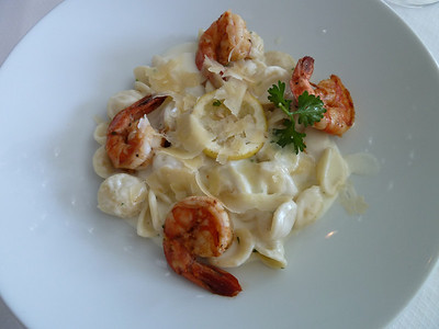 Orecchiette con scampi: shrimp with pasta rounds and parmesan cheese flakes