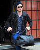 Non-Exclusive<br /> 2012 Oct 8 - Robert Pattinson exits his hotel with a leather duffel bag while listening to his iphone in NYC. Photo Credit Jackson Lee