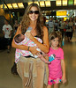 Non-Exclusive<br /> 2011 July 30 - Denise Richards feeds baby Eloise milk at JFK airport with daughters Sam and Lola. Photo Credit Jackson Lee
