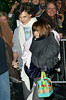 08 January 2009 - Suri Cruise gives an 'over-the-shoulder' while holding a case of bowling pins in the arm of mum Katie Holmes. Photo Credit Jackson Lee
