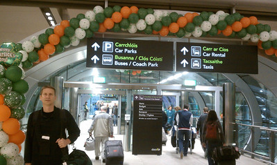 Dan at Dublin Airport - with English and Gaelic on the signs behind him.  Look at those people with all that luggage!  (Dan has a daypack and a duffle bag.  No purse.)