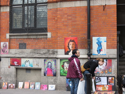 street artist selling her pictures.  I love the one top center with the red background.  Very cool.