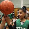 Lynn, Ma. 5-24-17. Keisha Perez gets a lesson on how to spin a basketball on her finger fron Lucky the Leprechaun during a basketball clinic held at the Lynn YMCA.