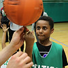 Lynn, Ma. 5-24-17. Kayshaun Fulton gets some instruction on how to spin a basketball on his finger from Lucky the Leprechaun at a Celtics basktball clinic held at thLynn YMCA.