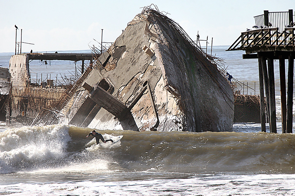 . A surfer rides a muddied wave in front of the broken, storm-tossed stern of the cement ship Tuesday morning.  (Dan Coyro -- Santa Cruz Sentinel)