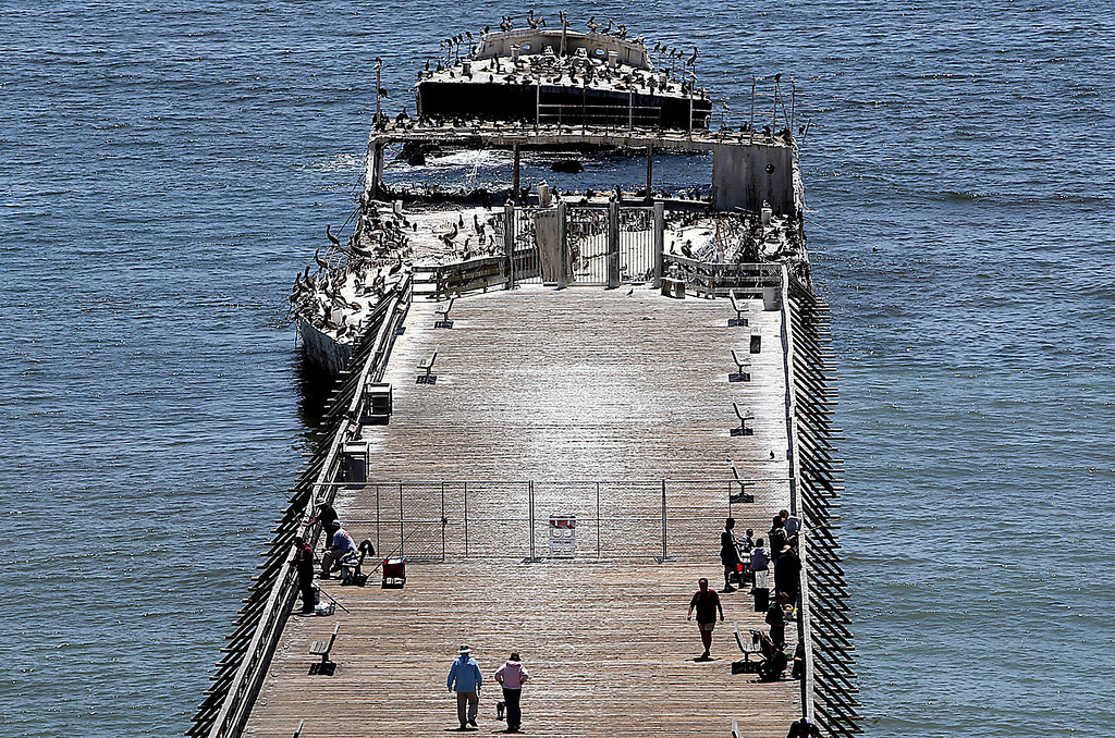 . Visitors walk along the pier leading to the SS Palo Alto in Aptos on Thursday afternoon. The pier is planned to reopen on Saturday as the decaying cement ship continues to settle. (Kevin Johnson -- Santa Cruz Sentinel)