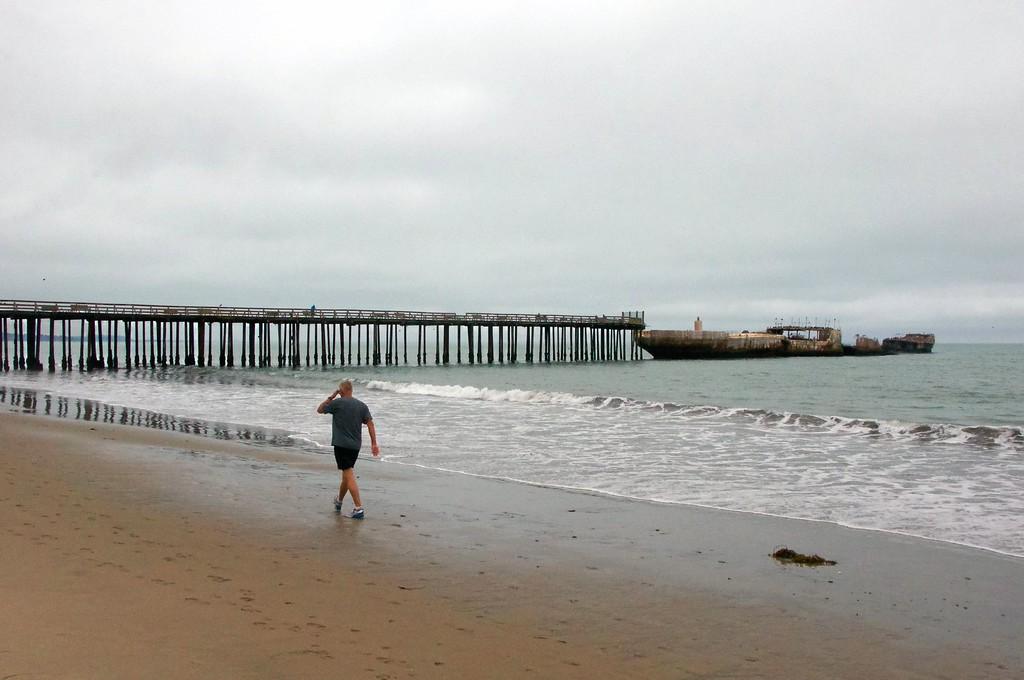 ". A beachgoer walks near the 96-year-old \""Cement Ship\"" at Seacliff State Beach (Mikaela Byers -- Santa Cruz Sentinel)."