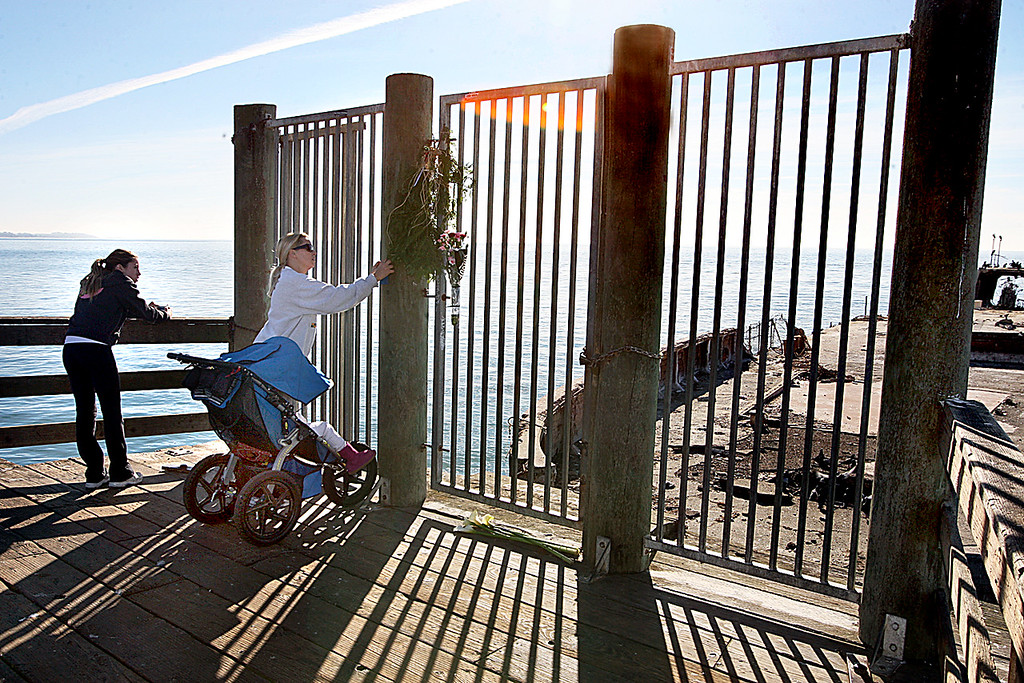 . Holly Johnson, wife of Aptos High Principal Casey O\'Brien, leaves a note at the Seacliff pier memorial for Aptos High student Nathan Phillips, whose body was found in the water next to the cement ship last Thursday.  (Dan Coyro/Sentinel)