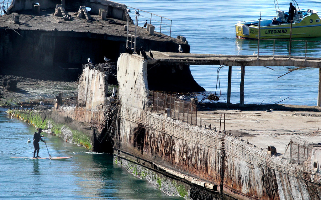 . A standup paddler and personnel aboard a lifeguard boat search around the cement ship at Seacliff State Beach Wednesday. (Shmuel Thaler/Sentinel)