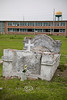 Above ground Graves in the Town of Buras with the Abandonment High School in the Background - Louisiana